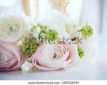 Lovely delicate elegant bouquet of flowers, buttercups and white lilacs, and two glasses of wine on a white painted wooden board, close up - stock photo