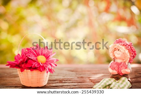 Lovely doll sitting and flowers in a Basket on a wooden with bokeh background in a vintage retro style, with the sunrise, for the day of love - stock photo