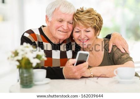 lovely elderly couple using smart phone at home - stock photo
