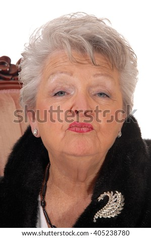 Lovely elderly woman giving a kiss in a closeup portrait image, with graywhite hair, isolated for white background. - stock photo