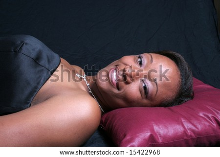 Lovely elegant black woman smiling and laying on a pillow - stock photo