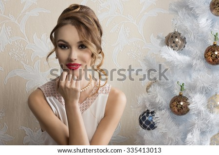 lovely elegant woman posing in romantic christmas portrait with hair-style, make-up and happy expression near decorated xmas tree