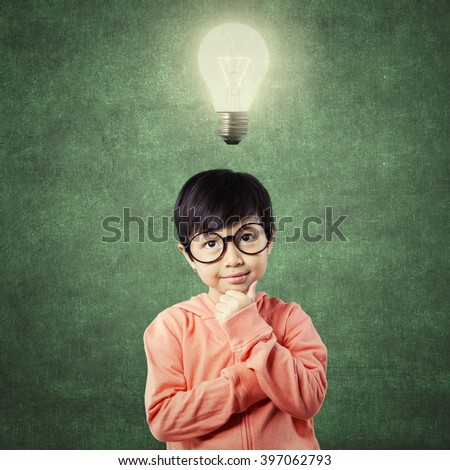 Lovely elementary school student standing in the class with thinking poses while looking up at bright light bulb