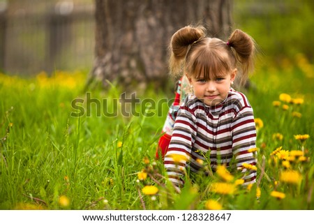 Lovely emotional five-year girl sitting in grass.