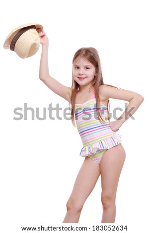 Lovely emotional little girl in modern swimsuit and straw hat isolated over white background/Fashion kid wearing swimsuit and straw hat posing on camera