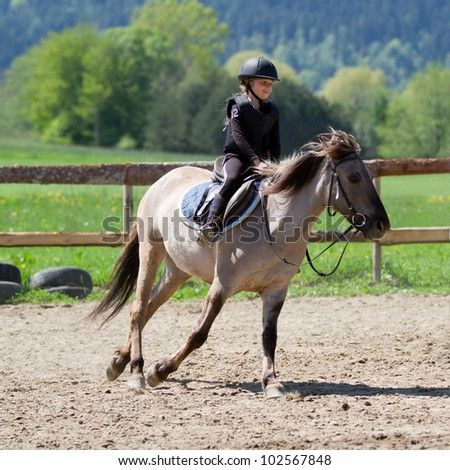 Lovely equestrian - little girl is riding a horse - stock photo