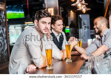 Lovely evening. Three friends men drinking beer and having fun together in the bar until one of them greeted the bartender