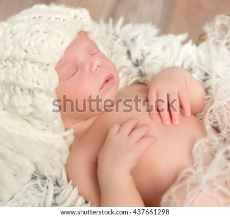 lovely face of newborn baby in knitted white hat lying on fur - stock photo