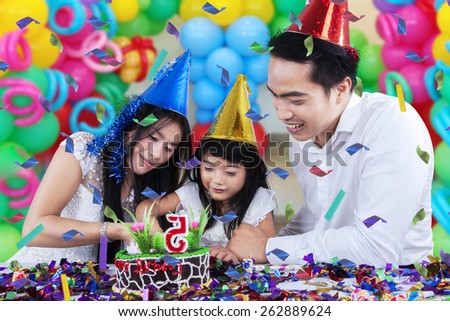 Lovely family celebrating birthday party and cutting a birthday cake together with colorful balloons background - stock photo