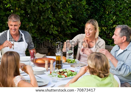 Lovely family eating in the garden - stock photo