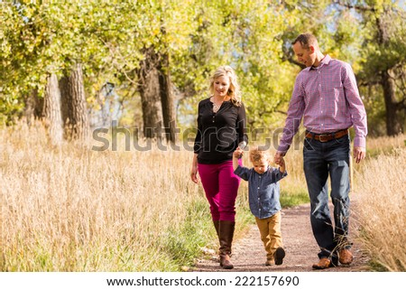 Lovely family enjoying weekend in open space park in early Autumn.
