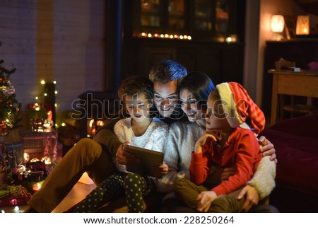 lovely family sharing digital tablet near the wood stove on a winter evening, enjoying the warm Christmas atmosphere in their living room, a child wears a hat of Santa Claus - stock photo