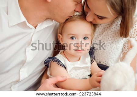 Lovely family smiling and laughing, posing at camera, and hugging each other for family photo