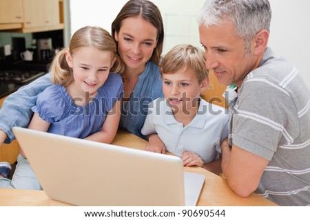 Lovely family using a laptop in their kitchen