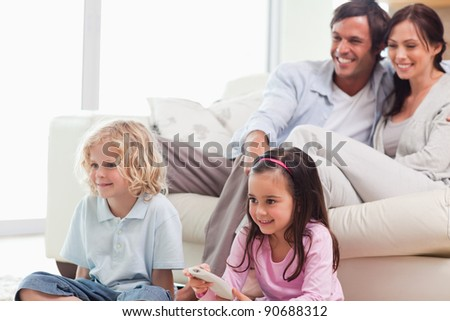 Lovely family watching a movie in a living room - stock photo