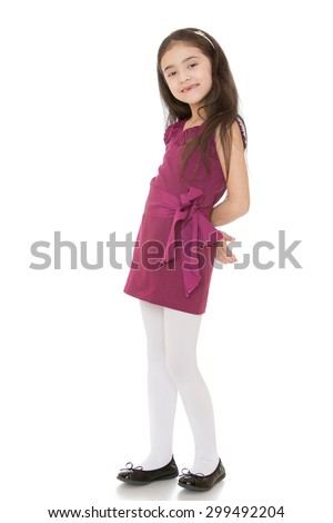 Lovely fashion small girl Oriental appearance with long dark hair on the head and the rim that holds the hair in a short brown dress and white tights smiles sweetly at the camera with his hands behind - stock photo