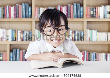 Lovely female elementary school student reading a book on desk while wearing eyeglasses in the library - stock photo
