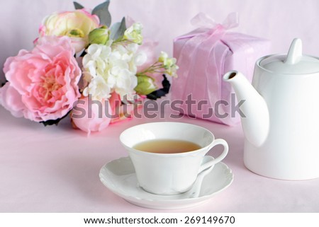 Lovely floral arrangement with pretty pink gift and elegant cup of tea for Mother's Day - stock photo