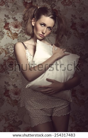 Lovely, fresh, pretty woman has got nice ponytails and cute make up, wears beige pajamas and holding a pillow.
