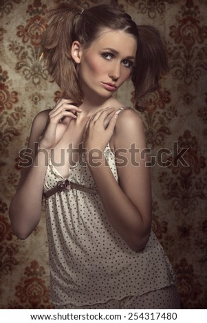 Lovely, fresh, pretty woman in beige pijamas. She has got nice ponytails and cute make up.