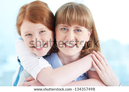 Lovely girl and her mother looking at camera with smiles - stock photo
