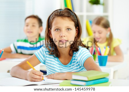 Lovely girl being busy with acquiring knowledge - stock photo