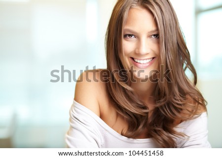 Lovely girl dressed in top with a wide neck looking at camera with a smile - stock photo