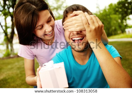Lovely girl giving her boyfriend a present - stock photo