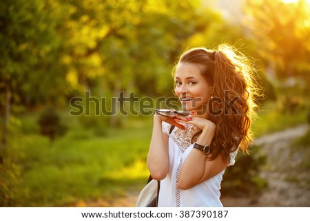 Lovely girl hippie walks in the park at sunset. Warm toning. Cute portrait.