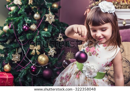 Lovely girl in a festive interior near a Christmas tree holding a Christmas decoration toy. Looking down. Merry Christmas and happy New Year! A series of photos - stock photo