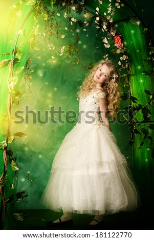Lovely girl in a lush white dress stands under a floral arch over green background.