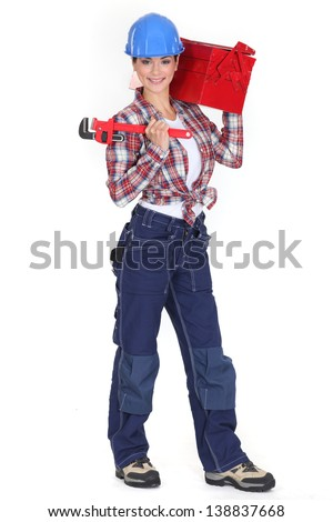 lovely girl in her twenties holding adjustable spanner and carrying toolcase - stock photo