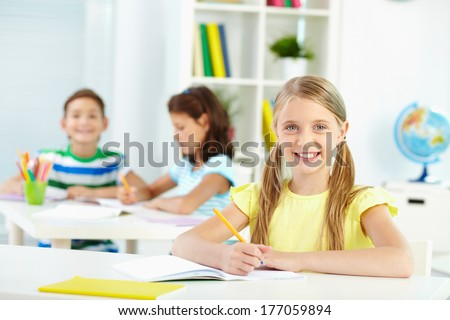 Lovely girl looking at camera with smile during lesson - stock photo