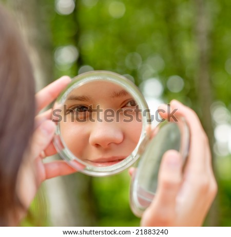 Lovely girl looks in round mirror against summer green park. - stock photo