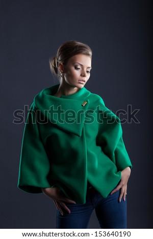 Lovely girl posing in trendy green coat, close-up - stock photo