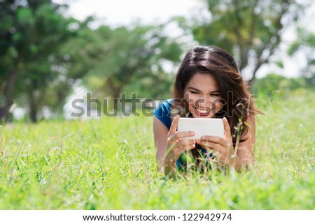 Lovely girl resting on the lawn and reading a funny text message