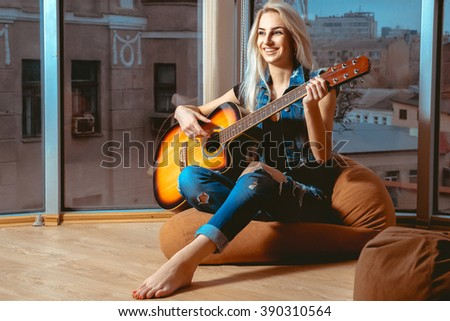 lovely girl smiling and having fun playing the guitar. Girl with guitar. Woman playing guitar. leisure with guitar. - stock photo