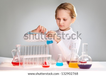 Lovely girl spending her free time in a school laboratory working with chemicals - stock photo
