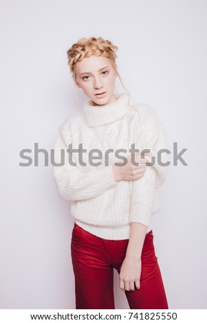lovely girl student in bright trousers and a warm winter sweater posing in Studio. funky hair and clean skin. emotional portrait
