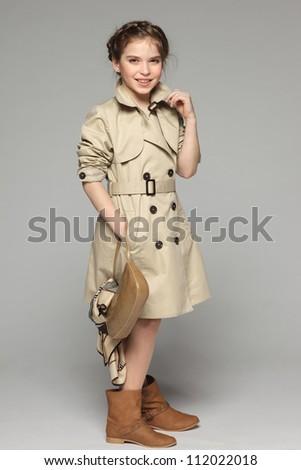 Lovely girl wearing beige trench coat holding handbag, over gray background - stock photo