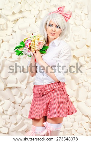Lovely girl wearing white wig and white blouse with plaid skirt posing over  background of white paper flowers. Anime style.  - stock photo