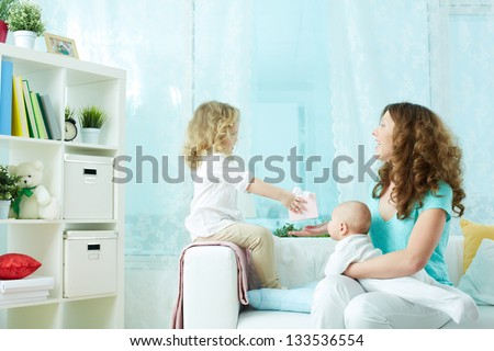 Lovely girl wishing her mother a happy mother�¢??s day and giving a present - stock photo
