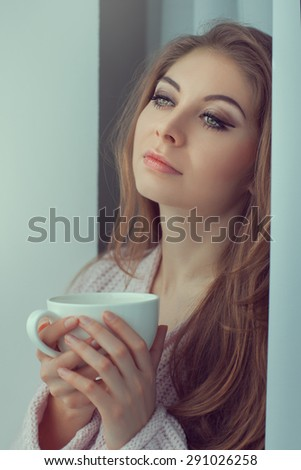 Lovely girl with a cup in his hands. Her sad and pensive eyes. Photo toned in vanilla color. - stock photo