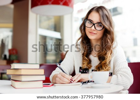 Lovely girl with brown curly hair wearing white sweater, glasses and watch sitting in cafe with cup of coffee, books and notebook, portrait.