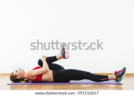 Lovely girl with light brown hair wearing snickers, dark leggings and red short top doing stretching at gym on purple mat, fitness, copy space, portrait.