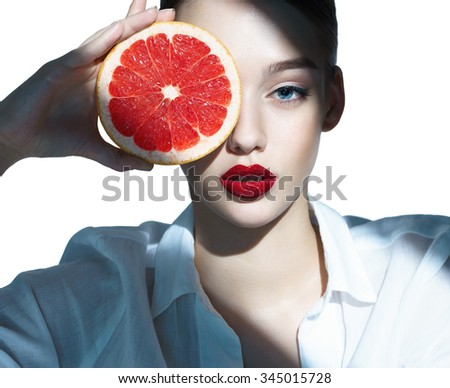 Lovely girl with pomelo slice, natural organic raw fresh food concept / close-up of an attractive girl of the European appearance in a white shirt - isolated on white background - stock photo