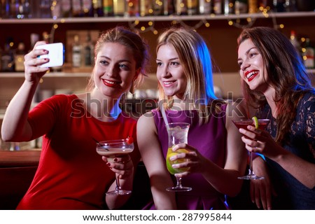 Lovely girls are taking a selfie in the bar  - stock photo