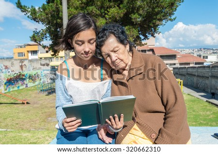 Lovely grandmother and granddaughter sitting together enjoying quality time outdoors reading in book. - stock photo