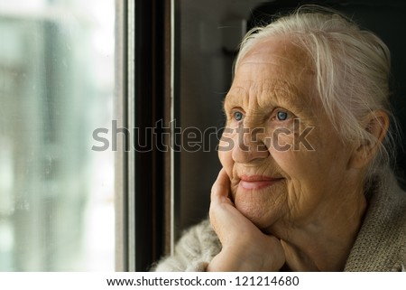 Lovely grandmother looking in a window, in a train - stock photo