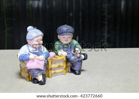 lovely grandparent doll siting wood chair on wood background with black background.